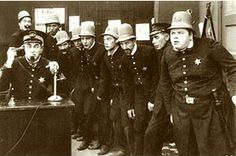 """The Keystone Kops in a typical pose in The Gangsters (1913). The desk officer using the telephone is Ford Sterling. The policeman directly behind Sterling (in extreme background, left) is Edgar Kennedy. The hefty policeman at extreme right is Roscoe """"Fatty"""" Arbuckle. The young constable with bulging eyes, fourth from right, is Arbuckle's nephew Al St. John. The casting of the Keystone police force changed from one film to the next; many of the individual members were per diem actors who remain unidentifiable."""