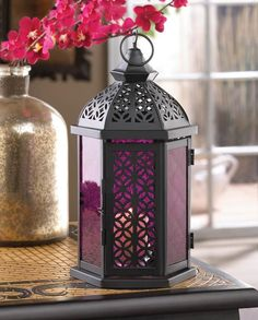 The brilliant color of this lanterns pressed glass panels will shimmer and shine, filling your room with candle light ambiance. The black metal framework features gorgeous cutout patterns that will cr