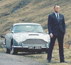Daniel Craig as James Bond in Tom Ford suit beside vintage Aston Martin DB5 in Skyfall (2012)