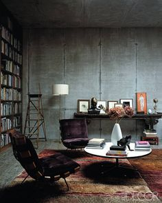 In the library, a pair of  vintage chairs is upholstered  in a purple velvet, and the console is from Bali.