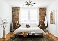 bedroom with exposed brick wall and tall white ceilings with modern pendant lamp / sfgirlbybay