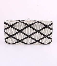 """This jeweled clutch evening bag has a beautiful crisscross design on the front. It is lined with silver lining and can be worn both as a clutch or a shoulder strap bag.European Crystal ElementsSize: 6.5""""L x 3.5""""H x 1.75""""WColor: Black and Silver"""
