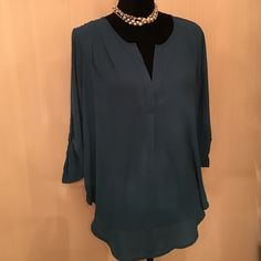 Tunic style blouse Brand new - never worn Stunning peacock color & flattering styled blouse with rolled button up sleeves. Super cute & I have a black one too - let's make a deal for 1 or both. Lush Tops Tunics
