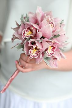 Flower girl wand of cymbidium orchids and silver senecio foliage. Liberty Blooms