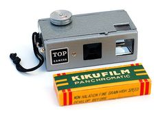"This is a Japanese subminiature camera, made c1965 by Maruso Trading Company. This example has ""instant"" and ""bulb"" shutter speeds and a dual finder (eye-level and reflex). There is another version with only the eye-level finder and a single-speed shutter. Believe it or not, this camera is made of bakelite, with a metal front and back. They applied a hammertone enamel finish to the whole thing, to make it look as though it's an all-metal camera. The box of film shown here is barely over two…"