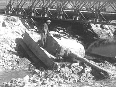 A destroyed Tiger 1 sits in a bomb crater being inspected by a British soldier.