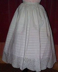 C.1850-1860. An early fullpetticoat that was originally worn over a horsehair crinoline, and then later used over the cage crinolines. It is gauged around the waistband for equal fullness all round (it is shown over a late elliptical crinoline which does not give it it's proper shape). The bottom of the skirt is decorated with pintucks and a wide panel of Broderie Anglaise. The right side of the skirt has a hidden pocket and the back fastens with a button.