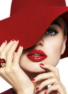 Mujer con sombrero rojo, uñas rojas y labios rojos.