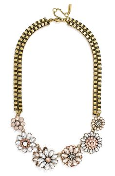 Antiqued box chains contrast beautifully with floral clusters of pastel crystals for an edgy-meets-ladylike look that will instantly brighten any ensemble.