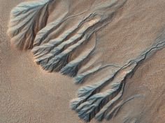 Similar to water-sculpted gullies on Earth, these gullies in Sisyphi Planum show well developed alcoves, deeply incised channels, and large depositional fans. These gullies could have formed under a different climate, or maybe by repeated bursts of transient fluids. Current leading hypotheses explaining the origin of gullies includes erosion from seepage or eruption of water from a subsurface aquifer, melting of ground ice, or dust-blanketed surface snow. | HiRISE