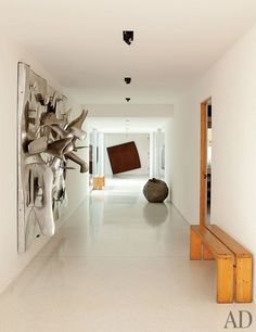 A gallery displays works by, from left, Étienne Hajdu, Ellsworth Kelly, and Lucio Fontana; the benches are by Perriand.