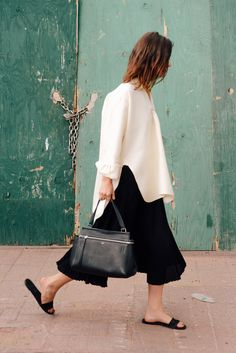 White oversized top, black skirt, black slides, black purse