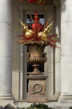 Oversized ornaments, gold sparkle sprays in an old urn...gorgeous.