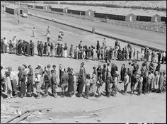 San Bruno, California. This assembly center has been open for two days. Bus-load after bus-load of evacuated persons of Japanese ancestry are arriving on this day after going through the necessary procedures, they are guided to the quarters assigned to them in the barracks. Only one mess hall was operating today. Photograph shows line-up of newly arrived evacuees outside this mess hall at noon. Note barracks in background, just built, for family units. There are three types of quarters in…