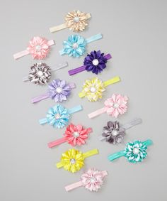 Gather up this bouquet of jewel-toned satin headbands to add a fabulous floral flourish to any little lady's ensemble. Stretchy, versatile and embellished with rhinestones, this pretty set will stay daisy fresh day after day.