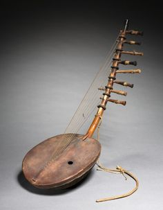 Musical Instrument, 1900s East Africa, Uganda, 20th century wood and leather, Overall - h:66.70 cm (h:26 1/4 inches).