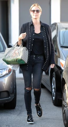 Quirky look: Heidi Klum stepped out in Beverly hills on Friday in a pair of distressed jeans, black wet look shoes and a funky cardigan featuring plenty of silver buttons