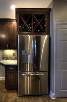 A custom wine rack above the refrigerator is a spin-off on the open shelving idea, and the gridlike pattern adds interest to the room. Because high temperatures can affect the aging process of wine, this idea works best above modern refrigerators where the coils are on the bottom of the fridge instead of on the back.