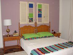 Quarto de hóspedes - janelas de demolição como decoração, pintura na parede com uma moldura branca, móveis da família sendo aproveitados.
