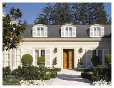 A single-story home in Atherton, California, this residence was designed to embody the look and feel of elegant French style. To do so, a mansard roof was utilized to create the illusion of a multi-story home with symmetrical segmented arched dormers. Front entrance and gardens. Photographer: Matthew Millman