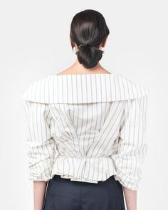 Le Top Marin in Off White/Blue Stripe by Jacquemus. A voluminous blazer in an off white color with blue pin stripes composed of a cotton and linen blend; features include large 3/5 sleeves with gathering at inseam, a large open shawl collar, a high low hem with a raised back hem, gathering at back and a tie belt running through blazer for adjustability at waist.  50% cotton, 50% linen  Dry Clean  Made in Bulgaria  $455