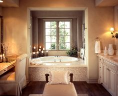 Luxury bathroom with mood lighting and enclosed soaker tub room with window and massage table