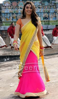 South Indian diva Hansika Motwani in flashy colors, wrapped in rising trend of half-saree. Lower half bottom is dipped in sweet pink with a creme trimming, upper body is hidden with yellow laced pallu and border, comes with a contrast orange round neck blouse.