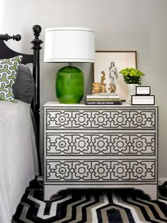 A chest of drawers doubles as a nightstand. Nailhead embellishments add visual interest to the front. - Traditional Home ®/ Photo: Emily Followill / Design: Melanie Turner