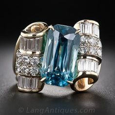 Blue Zircon and Diamond Estate Cocktail Ring - Price: $5,950.00 _ A magnificent deep Caribbean-blue scissor-cut zircon, weighing 9.50 carats, glistens diagonally between a pair of sparkling baguette and full-cut diamond scrolls in this dynamic and dazzling, one-of-a-kind showpiece. 2.10 carats total diamond weight. 11/16 inch high by 3/4 inch wide.