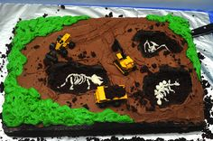 #dinosaur #birthday #cake dinosaur dig cake - chocolate cake dug out to reveal marshmallow fondant skeletons, decorated with construction equipment.