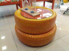 A mesa de centro foi criada a partir de dois pneus usados que foram pintados em dois tons (laranja e amarelo). Em cima o tampo de vidro  By Isa Perinotto