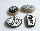painted pebble / small animals and plants from the ocean stylized in black and white