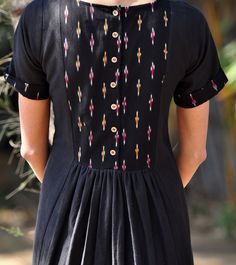 Our wear-everywhere black dress will instantly add an air of elegance to the room. The design features short sleeves and front and back yoke in ikat fabric. Pleated details along the waist add to the beautiful flare. The front slant pockets and buttoned back are a perfect blend of style and comfort