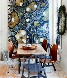 Abstract: The abstract painting on the wall does not represent anything specific. Also, the collage of mix matched chairs have an inviting yet random feel to them. The two together create an abstract interior.
