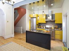 The sunny yellow cabinets make this small kitchen feel brighter. The sunny color, along with the industrial-style lighting, gray tile backsplash and stainless steel appliances creates a balanced, modern kitchen.