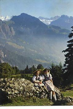 2 Cute Girls sit on Wall in the Alps Alpen