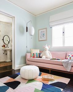 Mint walls! Benjamin Moore Green Cast LRV: 77. Rug is Land of Nod, pouf is Lulu & Georgia, couch is Target style (looks like it's reupholstered with Fabric cut fabric), wallpaper is Juju papers, lamp is Design Within Reach