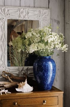 Bring the beach inside with a loose arrangement of wild flowers and grasses, alongside driftwood and seashells.