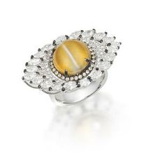 A cat's eye chrysoberyl and diamond ring The circular cat's eye chrysoberyl cabochon, weighing 12.00 carats, within a brilliant-cut diamond surround of brown hue, to a brilliant and marquise-cut navette-shaped diamond surround, mounted in 18k white gold.