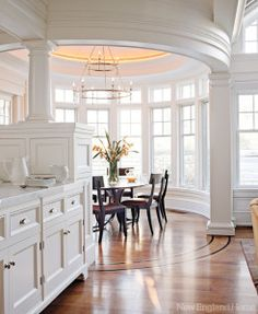 The angular coffered ceiling of the kitchen contrasts with the oval shape of the adjacent breakfast room.