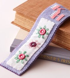 Personalized Bookmark - Cut lengths of felt to use as bookmarks. Layer pieces of felt and use decorative stitches to attach. Embellish the bookmarks with felt scrapbooking letters and buttons. For this design, we bordered one side of each letter with lazy daisy stitches and sewed on buttons surrounded by stitched-on petals.