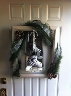 Wreath for front door... empty picture frame, garland, ribbon, pinecones, and an old pair of hockey skates