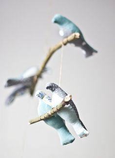 Najpiękniejsza z możliwych dekoracja do dziecięcego pokoju! Siedem ptaszków siedzących na gałązkach lekko porusza się przy najmniejszym ruchu powietrza. Ptaszki zostały uszyte z tkanin w kolorze seledynowym, białym, szarym błękitnym. Zawieszka pasuje zarówno do pokoju małej dziewczynki jak i małego chłopca, ale także sprawdzi się w innych pomieszczeniach domu. Rozmiary dekoracji: dł: 39cm, szer: 24cm; wysokość pojedynczego ptaszka to około 12cm.     pamiętaj: to ozdoba, nie zabawka!