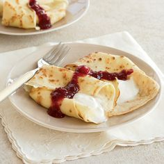 Crêpes with Sweet Yogurt and Raspberry-Apricot Sauce | These crêpes are like free-form blintzes, with thick and creamy Greek-style yogurt standing in for the cheese filling and a quick topping made with preserves and frozen raspberries.
