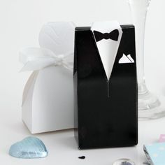 Dress up treats and mementos by placing them inside formal tuxedo favour boxes. Tuxedo boxes feature stand-up collars and lapels. These boxes cannot be personalised. Each pack contains 25 favour boxes.