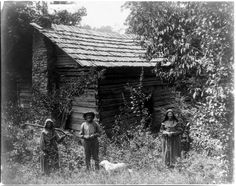 Circa 1910, Anderson County, Tennessee. Faust family and cabin home. Photograph shows Mary Faust, far right, standing in the back of cabin with man and another woman who is holding a rifle over her shoulder. M. H. Gass LC-USZ62-13607 www.loc.gov #American #History #Tennessee