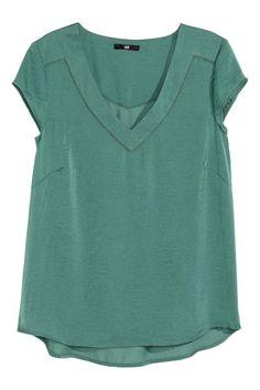 Blusa em cetim com decote em V e mangas curtas. Tem pormenor bordado em ponto de ajour na parte superior e corte arredondado na base.
