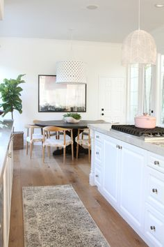 White and marble kitchen with a vintage rug and round table dining area  Photography : Becki Owens Read More on SMP: http://www.stylemepretty.com/living/2016/11/18/tour-a-bright-white-kitchen-with-modern-details/