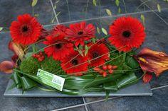 Modern bloemstuk...met rode gerbera's.