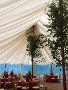 Draped ceiling of a Sperry tent from one of our weddings in June! The trees on the tent poles and the deep reds, purples, and golds gave the reception an enchanted forest feel. So cool! #realwedding #love #sperry #weddingbelle - For more ideas and inspiration like this, check out our website at www.theweddingbelle.net